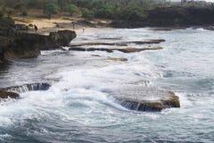 反对水和海的巨大的岩层有波浪的 库存图片