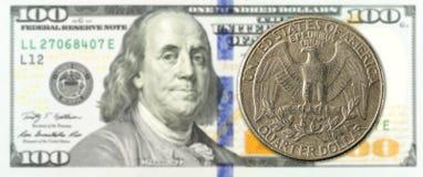 反对100我们美元钞票正面的四分之一美元硬币 库存照片