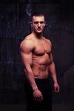 反对黑暗的墙壁背景的英俊的胸部赤裸的肌肉人 免版税库存照片