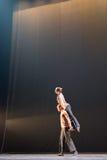 反对黑暗的背景的两2位舞蹈家姿势在阶段 免版税库存照片