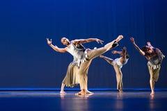 反对黑暗的背景的四位舞蹈家姿势在阶段 免版税库存图片