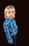 反对黑暗的背景的庄严的小男孩 免版税图库摄影