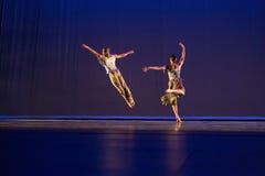 反对黑暗的背景的2两位舞蹈家姿势在阶段 图库摄影