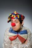 反对黑暗的背景的滑稽的小丑 库存图片