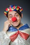 反对黑暗的背景的滑稽的小丑 免版税库存图片