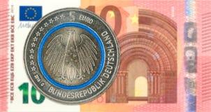 反对10欧元钞票正面的5枚欧洲硬币 库存照片