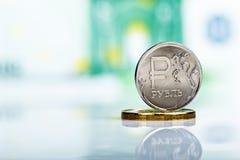 反对100欧元钞票的俄罗斯卢布硬币 免版税库存图片