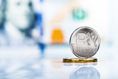 反对100的一枚俄罗斯卢布硬币美元钞票 免版税库存照片