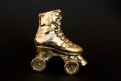 反对黑背景的金黄溜冰鞋 免版税库存图片