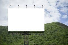 反对绿色山和蓝天背景的空白的大广告牌,您的广告的,投入了您自己的文本这里 库存图片