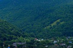 反对绿色山背景的村庄  美好的r 免版税库存图片