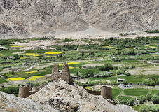 反对绿色村庄的古老城堡山的 免版税库存照片