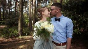 反对绿色树背景的年轻美好的夫妇新婚佳偶亲吻在公园 股票视频