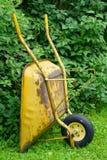 反对绿色灌木的独轮车 库存图片