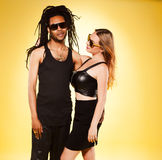 反对黄色的逗人喜爱的年轻混杂的夫妇 免版税库存照片