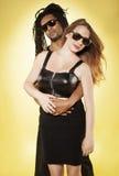 反对黄色的逗人喜爱的年轻混杂的夫妇 免版税库存图片