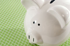 反对绿色背景的存钱罐 免版税库存图片