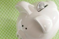 反对绿色背景的存钱罐 库存图片