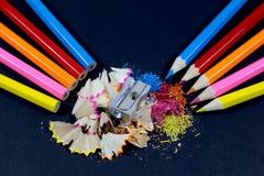反对直言的铅笔的被削尖的五颜六色的铅笔有金属铅笔刀的和在黑色的五颜六色的铅笔削片 免版税库存照片