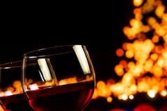 反对bokeh树的两块红葡萄酒玻璃点燃背景 库存照片