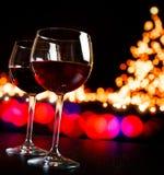 反对bokeh的两块红葡萄酒玻璃点燃树背景 免版税库存照片