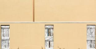 反对Tan背景的3个土气木闭合的门 免版税库存图片