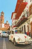 反对Taxco,墨西哥大教堂的微型出租汽车  免版税图库摄影