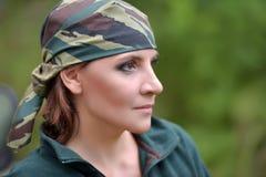 反对UAZ背景的妇女佩带的伪装班丹纳花绸  库存图片
