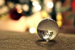 反射一棵被倒置的圣诞树的一个小的玻璃球的特写镜头在晚上 库存照片