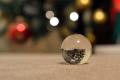 反射一棵被倒置的圣诞树的一个小的玻璃球的特写镜头 免版税图库摄影