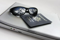 反射与护照和膝上型计算机的太阳镜斯诺伊山 免版税图库摄影