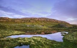 反射在一个小湖的岩石小山在与蓝天和阴暗云彩(法罗岛)的日落 库存图片