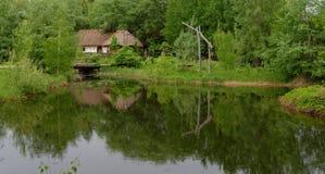 反射在一个池塘的农夫的房子在露天博物馆,基辅,乌克兰 库存照片