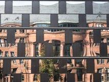 反射在一个现代大厦的窗口里的老大厦 库存照片