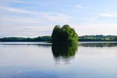 反射在一个蓝色湖的一个小绿色海岛 免版税图库摄影
