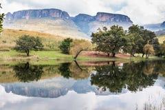 反射在与树和多云天空的水中的北德肯斯伯格山 库存照片