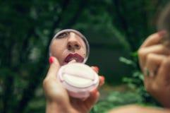 反射在协定的镜子的嘴唇,与红色唇膏的女孩染料 背景的一个绿色公园 免版税库存照片