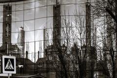 反射在新的大厦镜子墙壁的老城市  库存图片