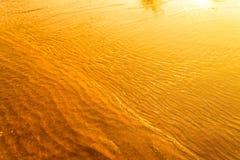 反射在日落的水波在海和沙子的金黄光 免版税库存图片