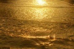 反射在日落的水波在海和沙子的金黄光 免版税库存照片