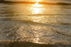 反射在日落的水波在海和沙子的金黄光 库存图片