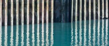 反射在水中的生锈的防波堤 免版税库存照片