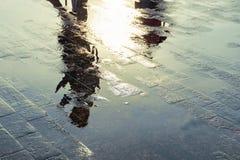 反射在水坑的人的剪影在雨以后 免版税库存照片