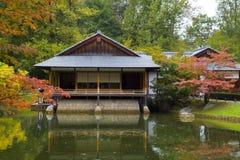 反射在池塘的茶屋在日本庭院里 库存照片