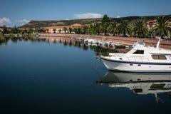 反射在河的博萨、撒丁岛和游艇看法  免版税库存照片