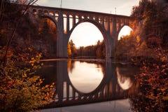 反射在河的桥梁在与秋天叶子的日落 免版税库存照片
