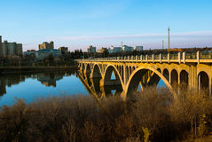 反射在河玻璃状的表面的一座金黄桥梁在日落 免版税库存图片