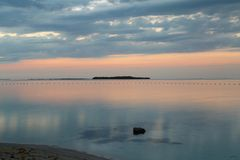 反射在海滩长的曝光的桃红色日落 图库摄影