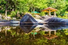 反射在湖中水的亭子、雨林和石头热带山的 免版税库存图片