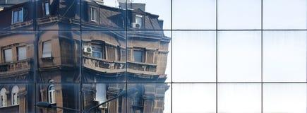 反射在现代玻璃建筑学的城市老新古典主义的大厦 免版税库存照片